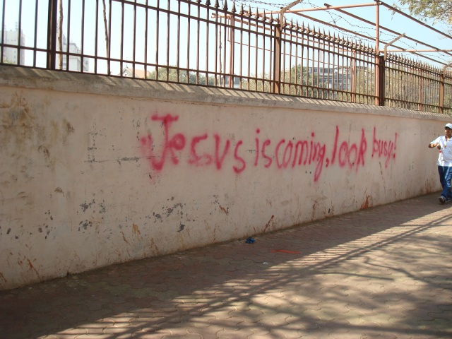 """A concrete wall with the graffiti slogan. """"Jesus is coming, look busy""""."""