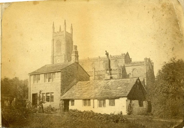 The earliest known photograph of Holy Trinity Church, Huddersfield, A sepia picture showing the chuch surrounded by fields.
