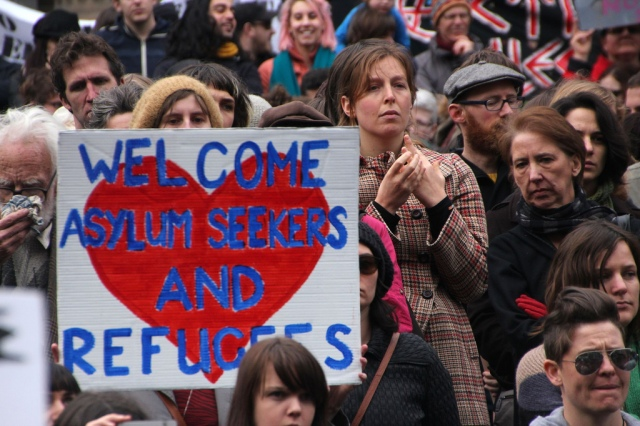 """A crowd of protesters, looking concerned. A banner has a red heart on a white background and this slogan in blue, """"Welcome Asylum Seekers and Refugees""""."""