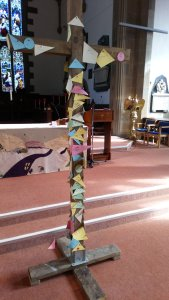 A large wooden cross in front of the altar in an Anglican church, with pieces of paper pinned to it depicting the sins on the congregation.