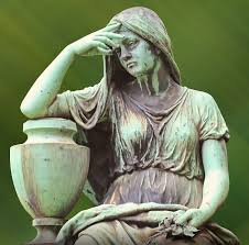 An old statue of a depressed woman leaning on an urn against a green background.