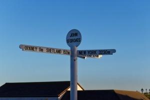 Signpost at John O'Groats, Scotland against a clear blue sky.