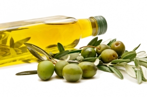 A bottle of olive oil lying on its side behind a few olives on sprigs against a white background.