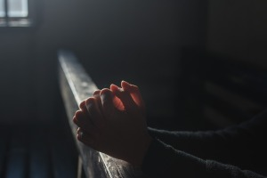 In a dark room a pair of hands rest on a wooden rail. The hands a clasped in prayer and lit from within.