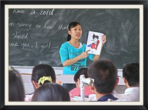 A teacher holding an illustration of a boy stands in front of a class of children, the background is a chalkboard.
