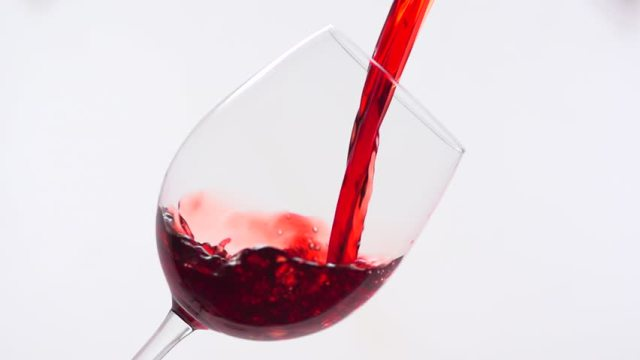 Red wine being poured into a glass.
