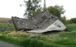 A collapsed house beside a road on moorland.