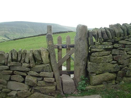 A narrow gate in a dry stone wall leads to the field beyond.