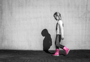 A girl wearing pink wellington boots is walking away, looking sad.