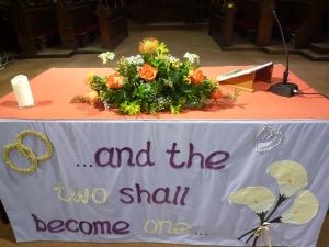 Flowers on a church altar. The altar front reads