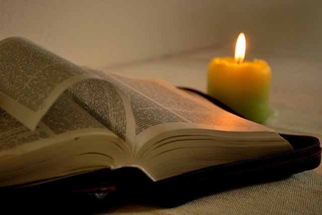 An open Bible next to a candle.