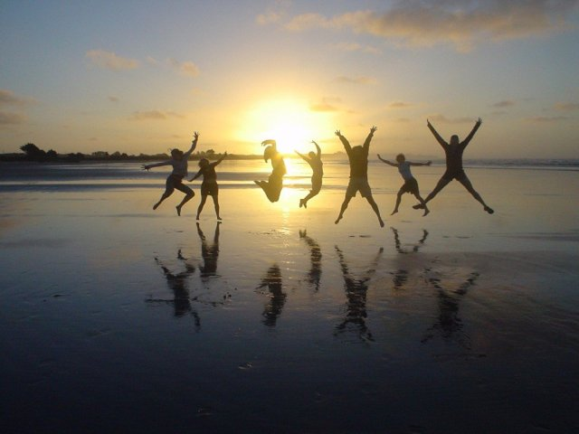 Seven people jumping for joy, silhouetted against a sunset.