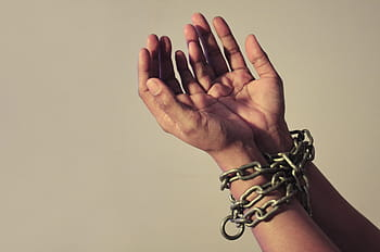 A pair of hands, bound at the wrist by a chain. The hands are cupped and facing upwards.
