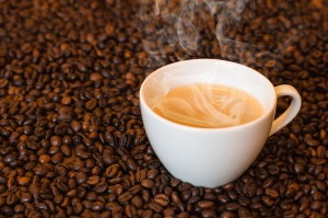 A white cup of coffee with steam coming off sits among roasted coffee beans.