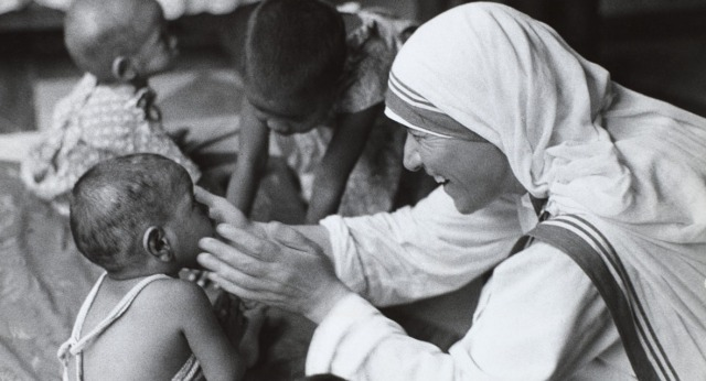 A smiling nun, Mother Theresa of Calcutta, looks on a small chi