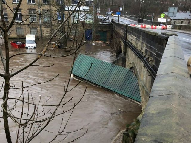 Shipping container on floodwater, stuck under the arches of Elland Bridge.