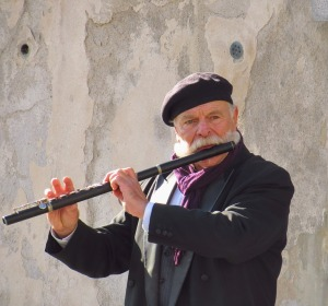 An old man with a white moustache playing a flute