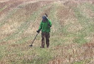 A metal detectorist in a field of short grass.