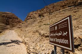 "A ridge of bare rock under a blue sky. In the foreground is a sign written in Arabic script and English saying ""Mount of Temptation"".d"