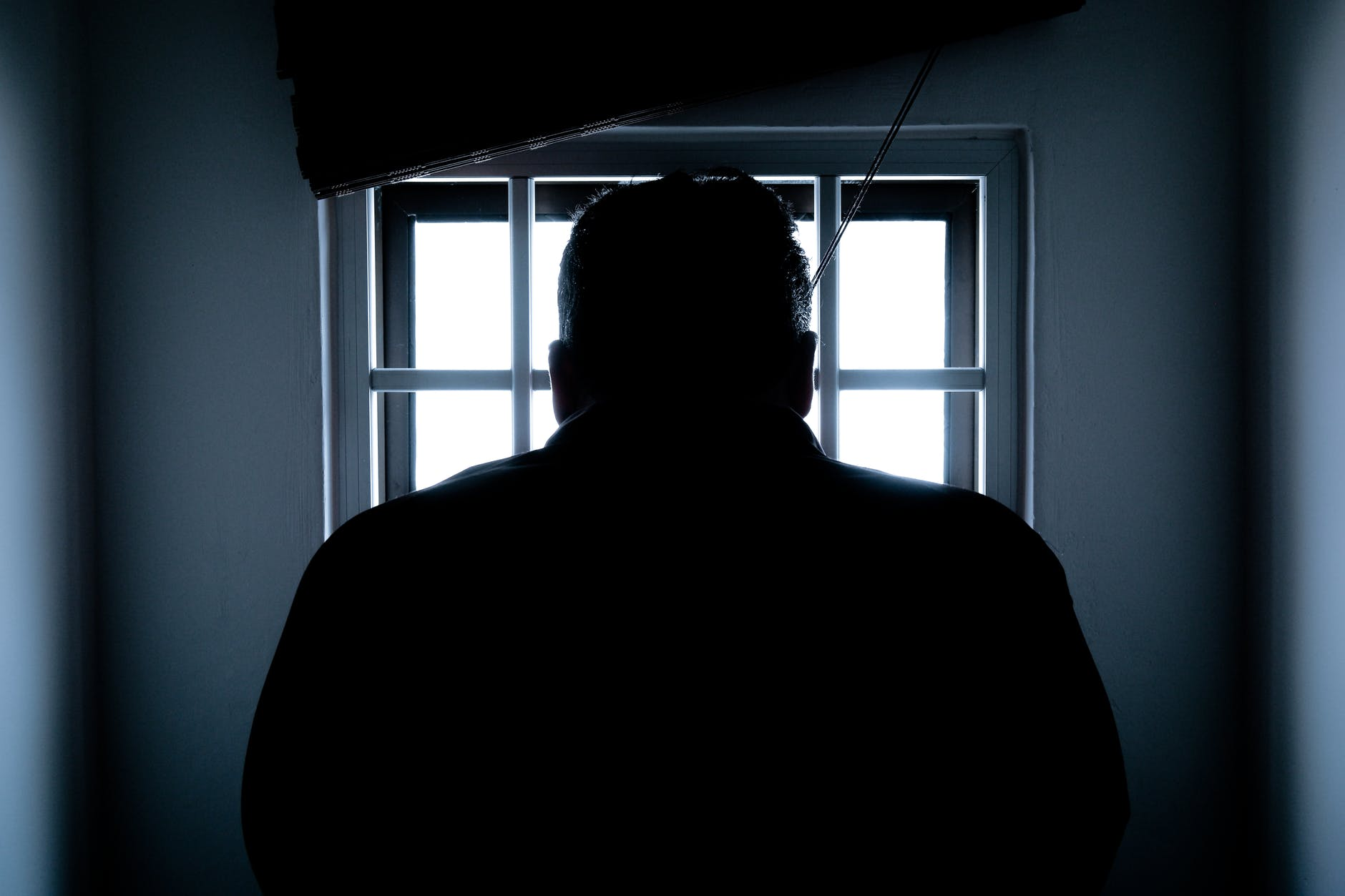 A large man is silhouetted against a barred window, probably a prison cell.