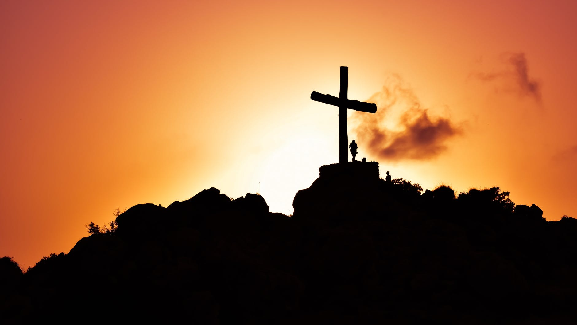 A silhouette of  a cross against the orange sky of a sunrise.