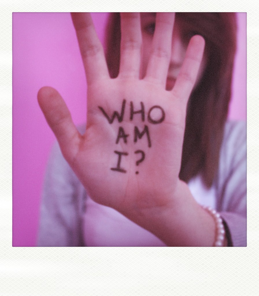 """A woman dressed in a grey cardigan over a pale pink top against a darker pink background raises her left hand in front of her face. Across the palm is written  in Capitals in black, """"WHO AM I?"""""""