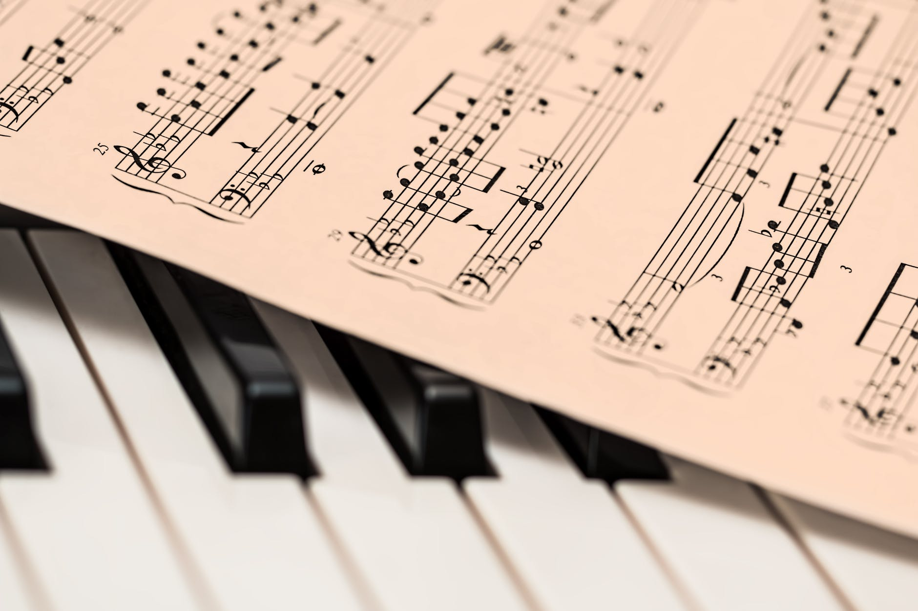 Piano keys upon which is laid sheet music in the key of E flat, printed on pink paper.