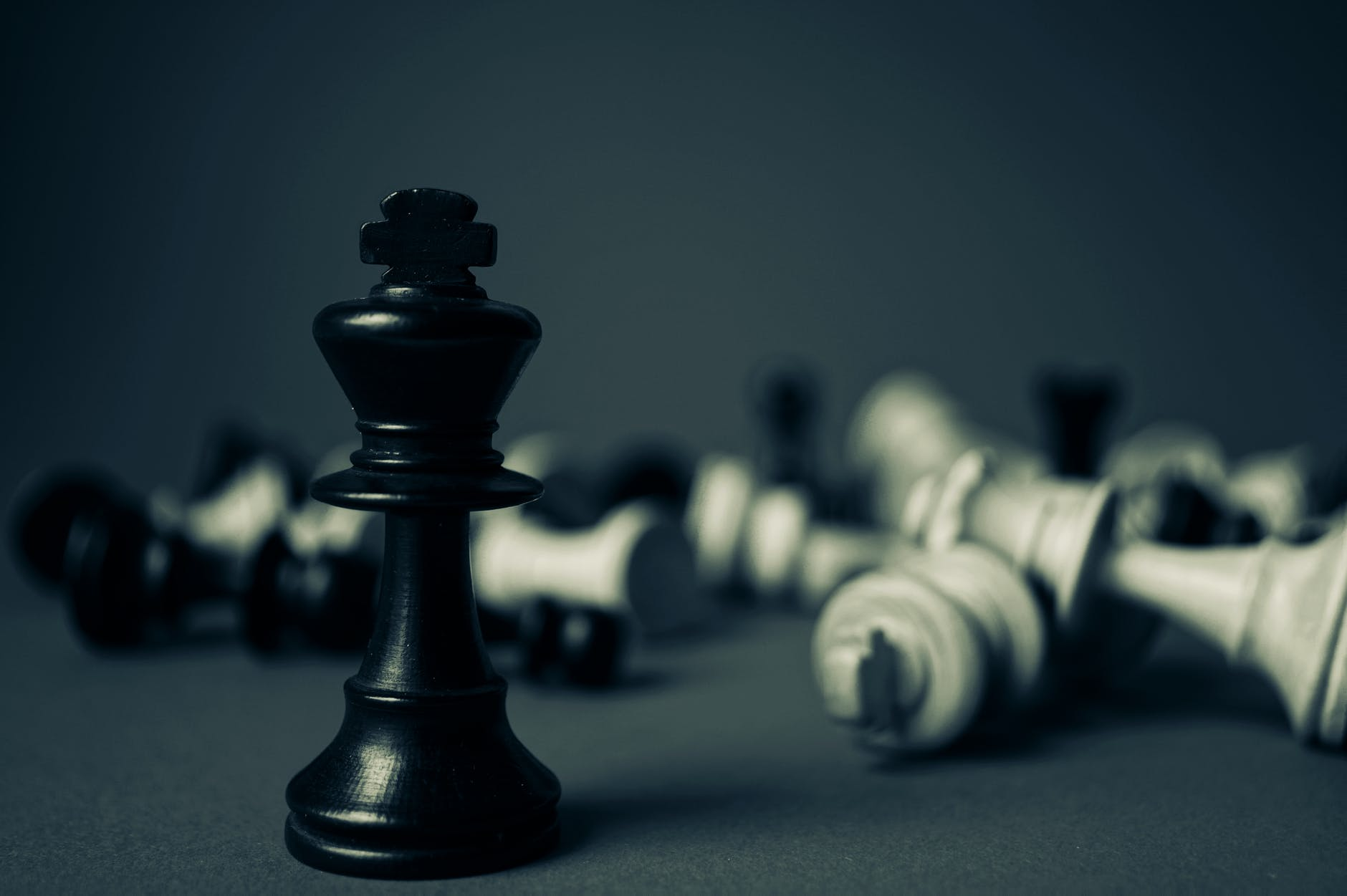 Chess men: The black king stands upright above other chess men on their side, including the white king.