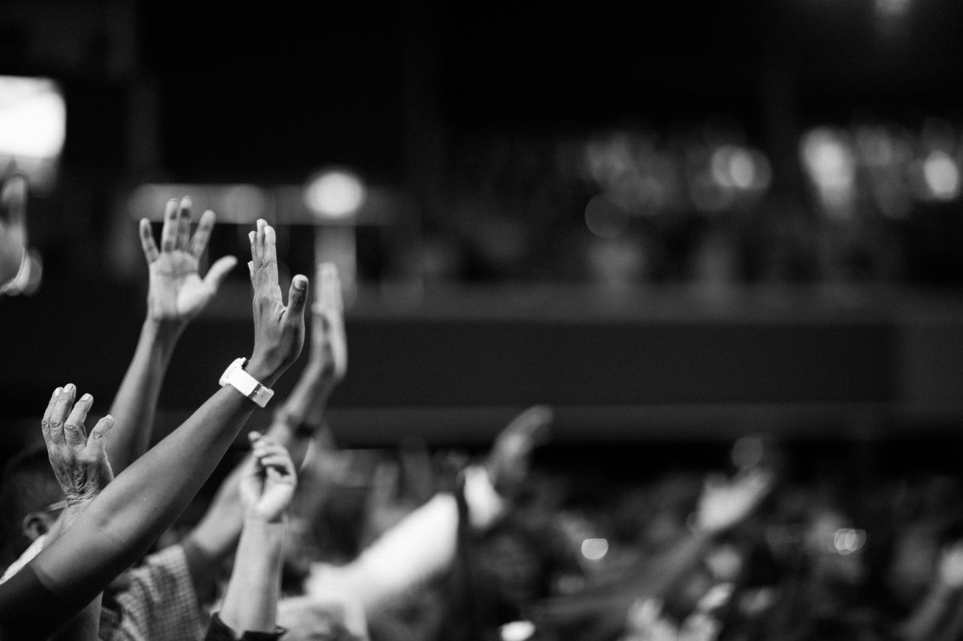 A black and white picture of hands raised in worship.