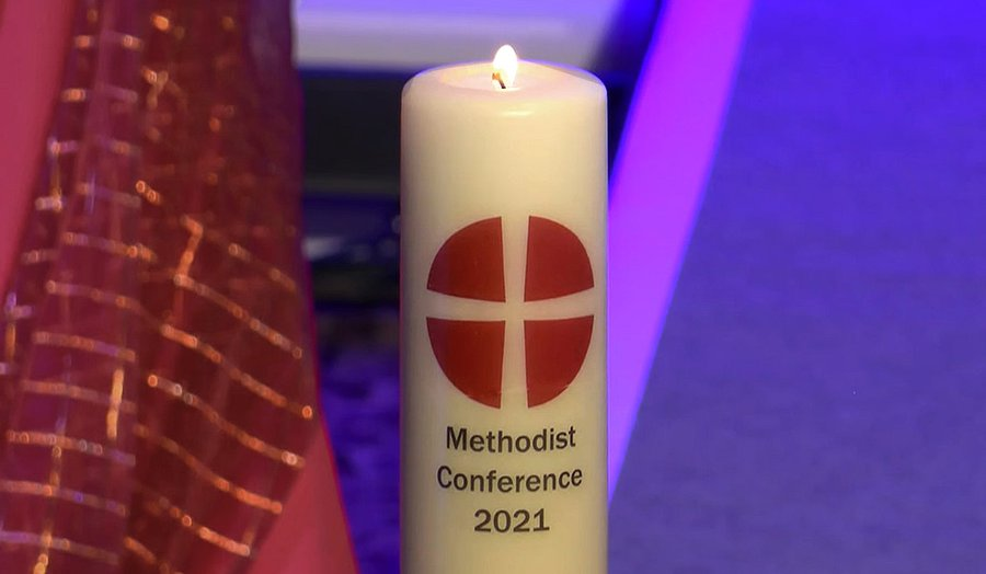 """An off-white candle with the symbol of the Methodist Church, a withe cross on a red circle, and the wording """"Methodist Conference 2021."""""""
