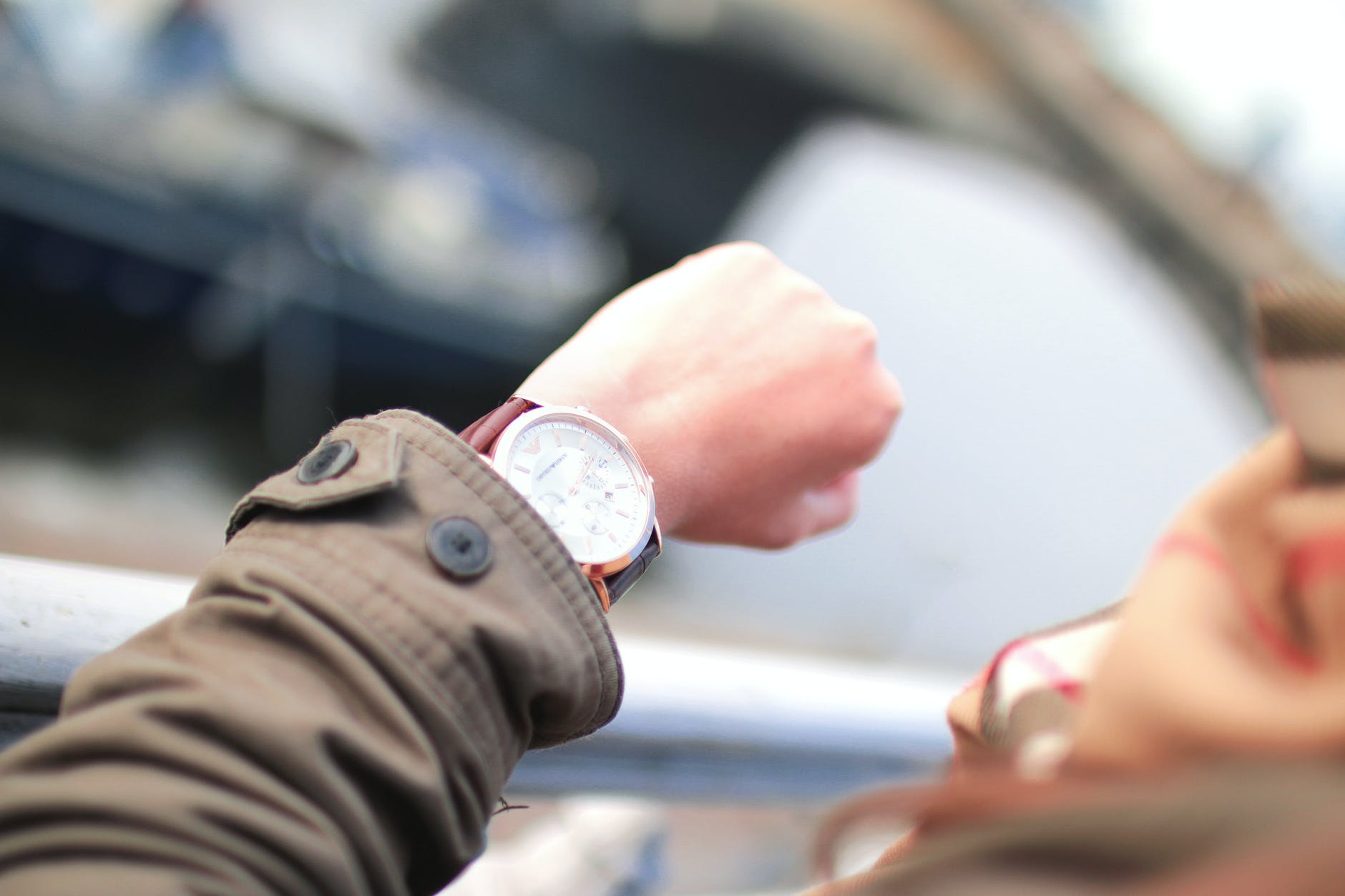 A man looks down on his wristwatch, waiting.
