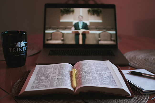 An open bible and a notebook and pen are in the foreground in front of a laptop on which is a picture of a church sanctuary in which a man in protestant robes appears to be preaching.robes is seen